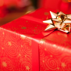 A Christmas present wrapped in red paper with a gold bow.