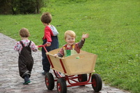 children playing with wooden wagon