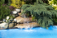 Water flows from a rock waterfall at the side of a swimming pool.