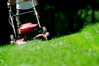 A mower cutting across a steep slope.