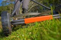 Close-up of push reel mower cutting grass.