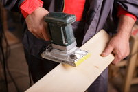 A DIYer working with a belt sander on a piece of lumber.