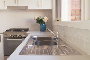 A stainless steel sink and oven in a white kitchen with flowers in a blue vase.