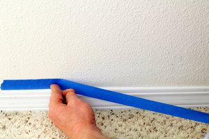 A DIY-er applying painter's tape.