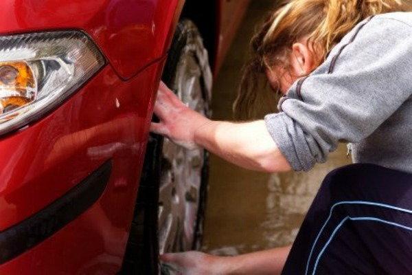 A woman washing a red car.