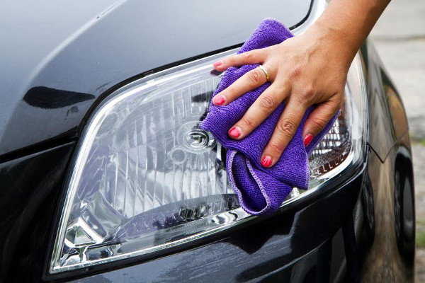 Cleaning the headlights on a car with a purple rag.