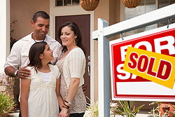 Family standing next a sold sign