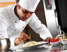 Chef garnishing plate of food