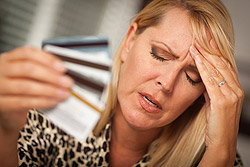 Upset woman holding credit cards