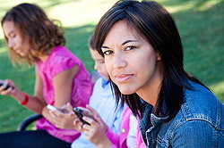 Concerned woman with girls on cellphones