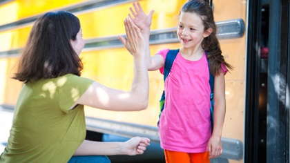 A mom giving her daughter a high-five near a school bus.