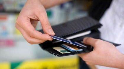 A woman pulls a credit card from her wallet.