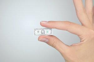 Hand holding a tiny dollar bill.