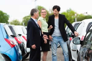 couple looking at cars with salesperson at dealership