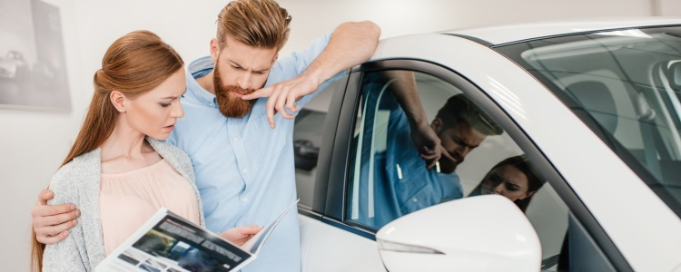 couple looking at car at dealership