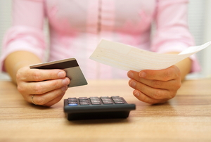 A woman holding a credit card in one hand and a bill in the other in front of a calculator.