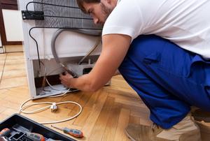 A repair man fixing a refrigerator.