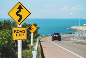 "A car drives on a windy road near the ocean. a yellow sign reads ""road trip"""
