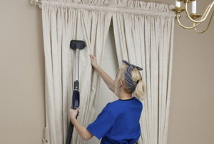 woman cleaning light-colored drapes