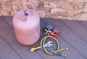 A Freon tank and gauges lay out on a deck.