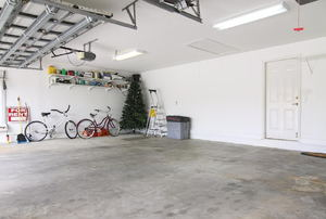 A garage with concrete floors and a few items stored to one side.