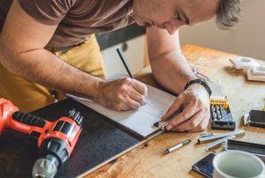 man planning home improvement at a workshop table