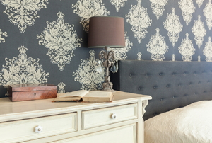 A bedroom with grey patterned wallpaper, a headboard with grey fabric, a cream dresser, and a lamp.
