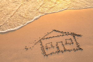 A house drawn in the sand with ocean water washing up toward it.