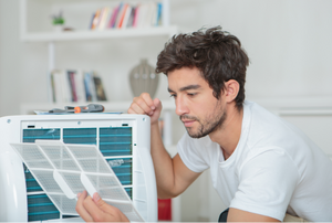 man looking a piece off the back of an air conditioner