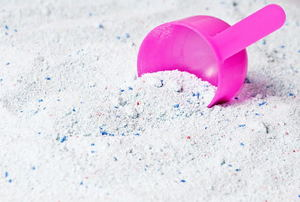 A pile of laundry detergent with a pink scoop.