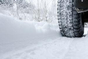 A close-up image of a car driving in snow with snow tires on.