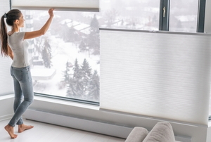 woman opening pleated blinds in front of snowy town