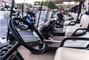 A long row of golf carts on a lot.