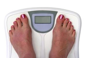 A person weighing themselves on a digital scale.