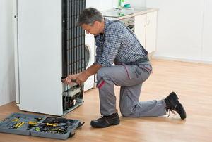 A man works on a refrigerator.