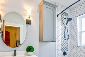 bathroom with drywall, mirror, and shower