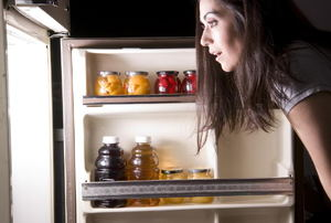 woman looking into an open refrigerator