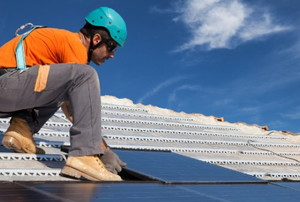 A worker lays solar panels on top of a roof.
