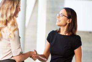 two women shake hands