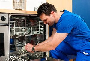 A technician diagnosing and repairing a broken dishwasher.