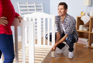 A couple works on a crib.