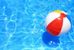 A beautiful pool with a floating beach ball, waiting to be splashed into.