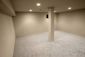 finished basement with carpeting floor and beige walls.