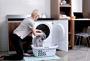 A woman on her knees putting laundry in a washing machine.