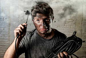 A man holding an electrical cord with smoke around his head.
