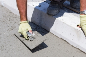 hands leveling freshly poured concrete