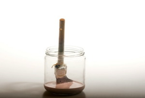 A paintbrush sitting in a glass jar filled in part with paint thinner.
