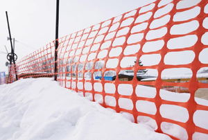 Orange snow fencing surrounded by snow