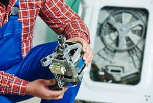 A man holds a washing machine motor.