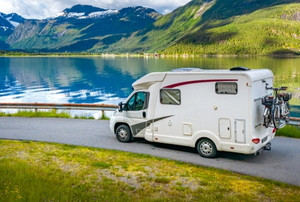 RV driving on beautiful road trip by lake